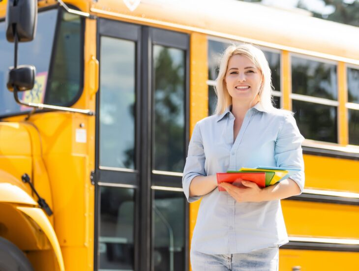 Teacher at school in front of the bus
