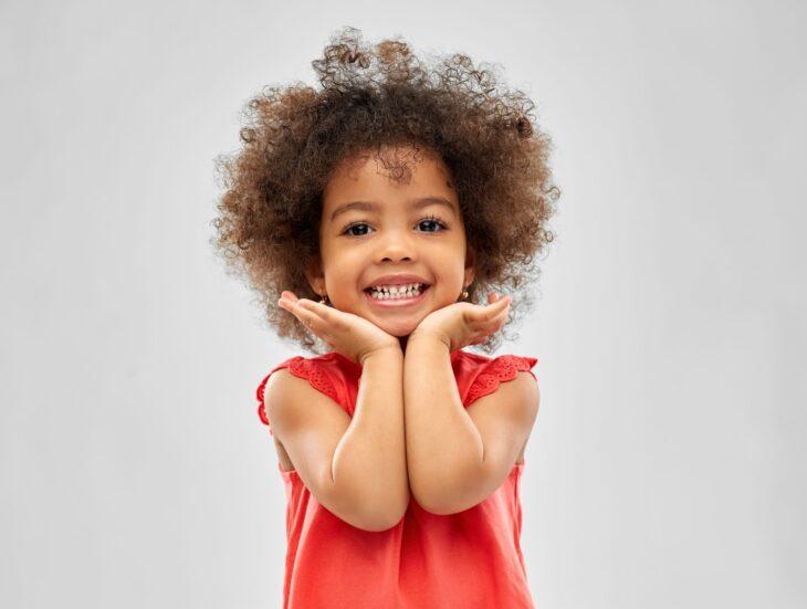 Happy little african american girl over grey