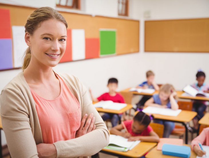 Female teacher smiling at camera at top of classroom