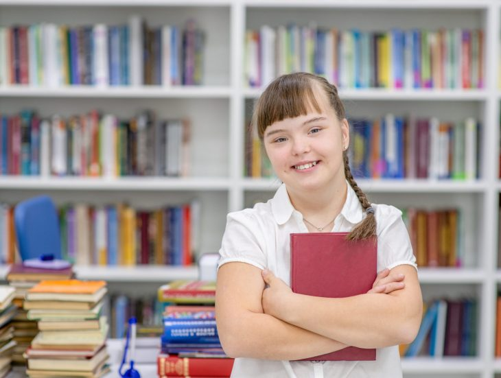 Portrait of a smiling girl with syndrome down at library. Empty space for text. Education for disabled children concept