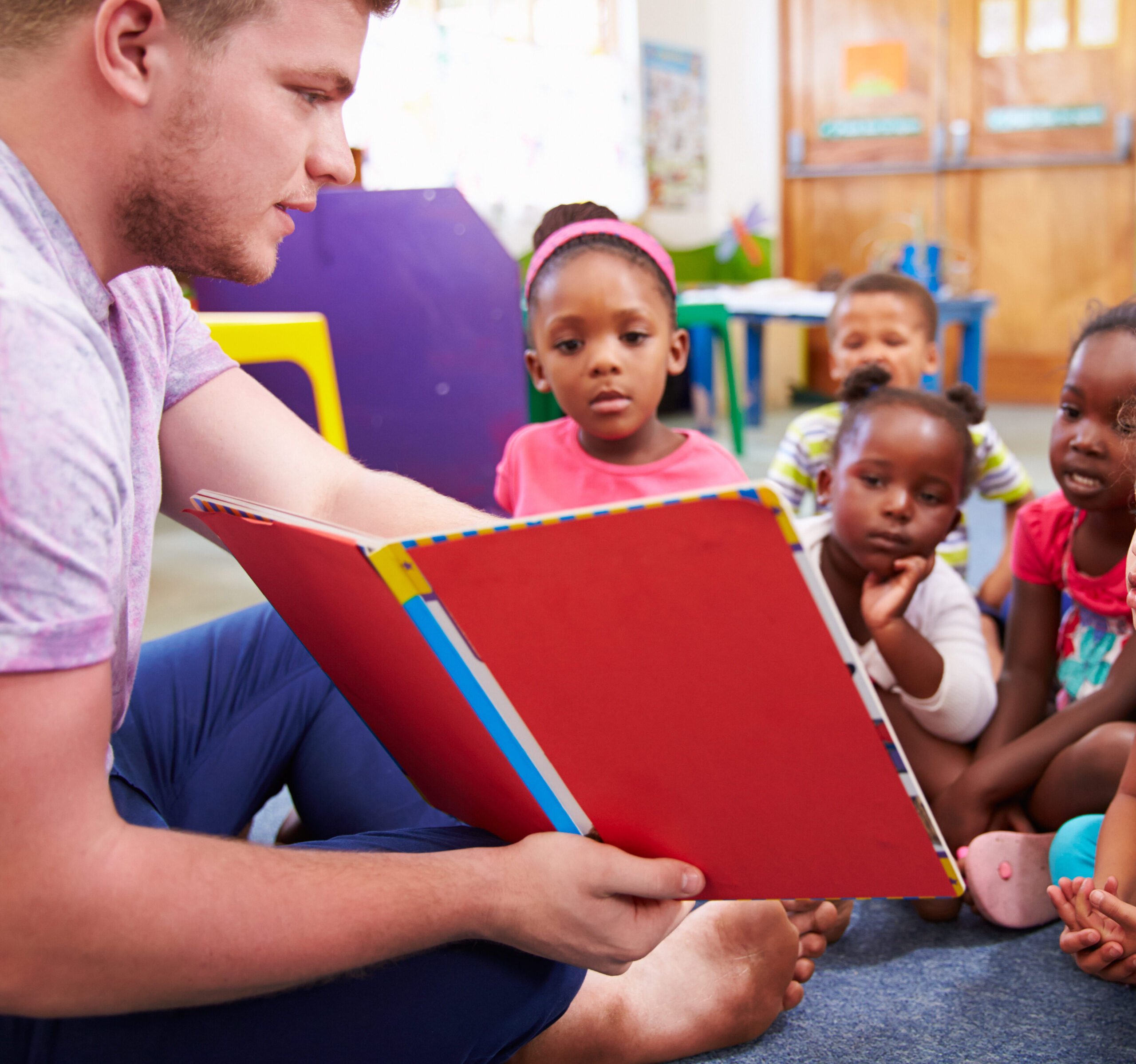 Male teacher with young kids scaled e1632406302267 aspect ratio 640 600